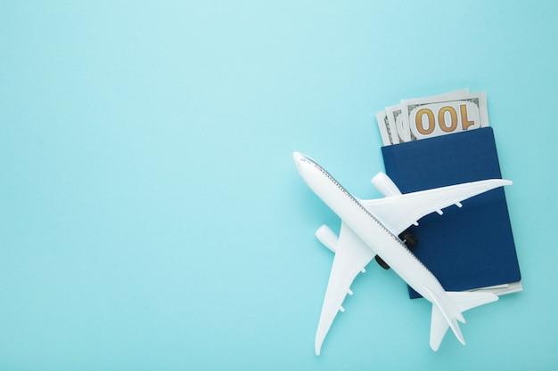 Preparazione per il concetto di viaggio, aereo, soldi, passaporto su sfondo blu con copia spazio. vista dall'alto