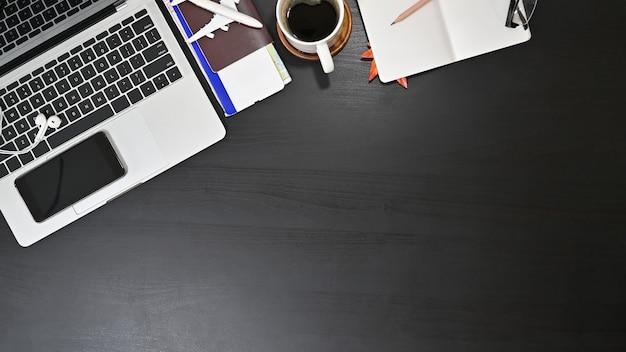 Preparare accessori da viaggio, vista dall'alto sul tavolo nero con spazio di copia.