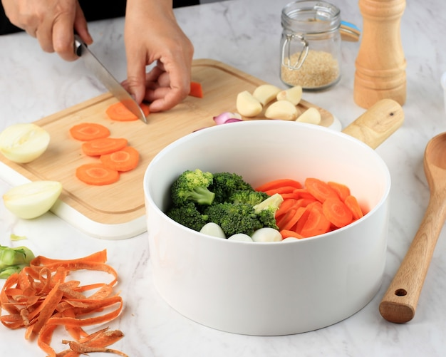 Preparare la cottura, affettare le carote sopra il tagliere di legno. mano femminile che cucina le verdure in cucina