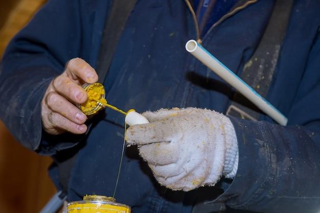Preparare un giunto di tubo con colla che sigilla i tubi in pvc della linea dell'acqua sulla nuova costruzione domestica