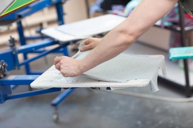 Prepararsi per la stampa e applicare il processo di stampa serigrafica serigrafica su tessuto presso la fabbrica di vestiti clothes
