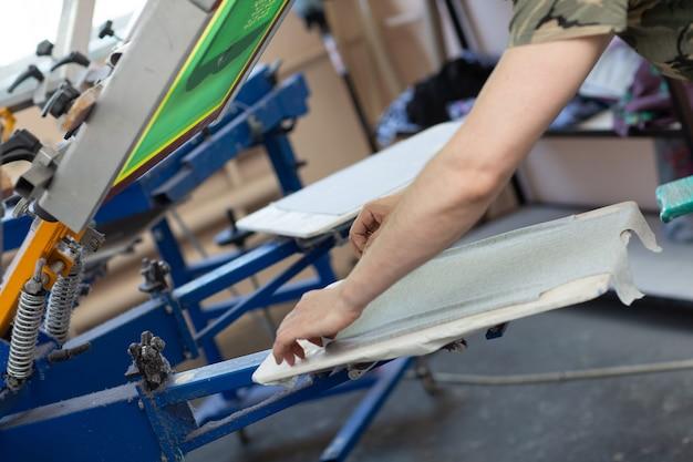 Prepararsi per la stampa e applicare il processo di stampa serigrafica serigrafica su tessuto presso la fabbrica di abbigliamento.