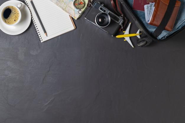Prepara una valigia, una macchina fotografica vintage, un taccuino, una mappa e un caffè nero sul pavimento piastrellato nero e copia lo spazio. concetto di viaggio