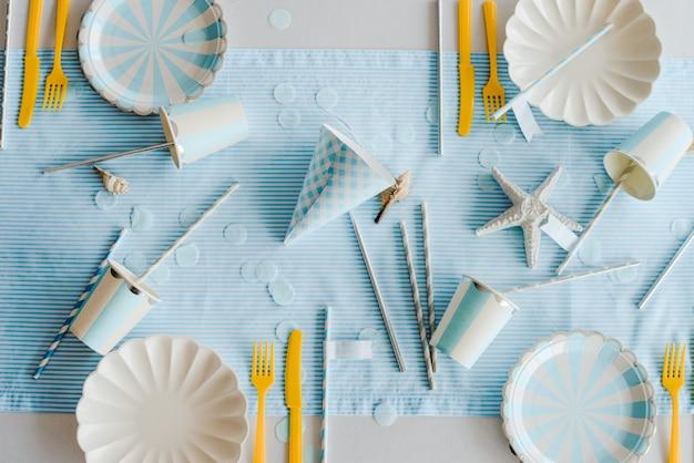Tavolo di compleanno preparato con stoviglie di carta elegante per la festa dei bambini nei colori blu e giallo. baby shower day, vista dall'alto