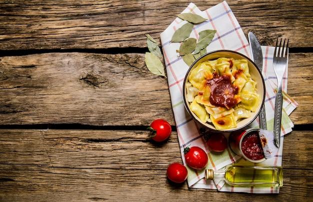 Ravioli preparati con salsa di pomodoro in una tazza. sullo sfondo di legno. vista dall'alto