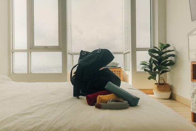 Preparare uno zaino nero per un viaggio in camera da letto.