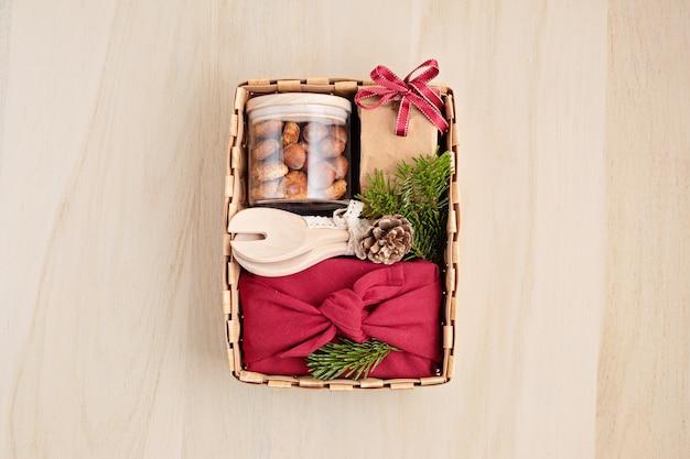 Preparazione del pacchetto di cura e confezione regalo stagionale con utensili da cucina, scatola furoshiki e biscotti