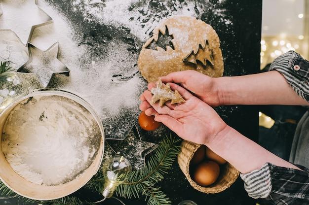 Preparando il biscotto di natale, vista superiore, retro filtro applicato, concetto domestico di natale su una superficie grigia