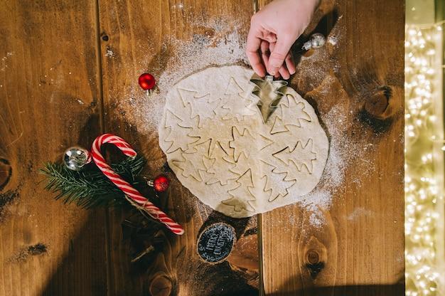 Preparare i biscotti di natale su una superficie di legno
