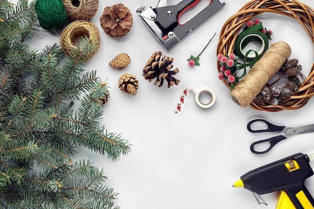 Preparazione per le vacanze di natale o capodanno flatlay di pelliccia rami di alberi ghirlande corda forbici artigianali...