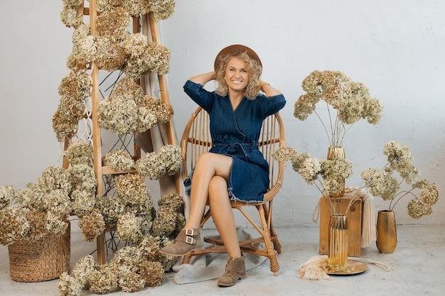 Preparazione dell'arredamento nello spazio aziendale, fiorista donna, seduta su una sedia realizzata con materiali naturali, tra fiori secchi. foto in studio