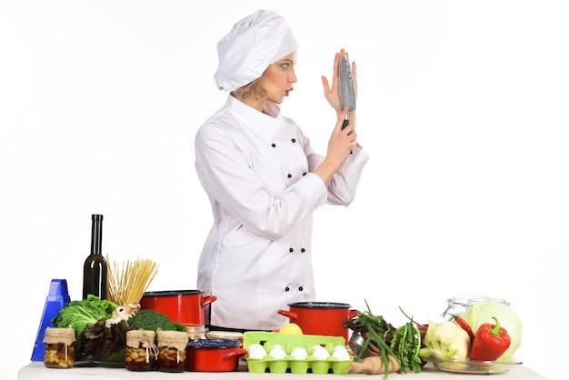 Preparazione dei piatti. giovane cuoca che prepara cibo delizioso in cucina. cuoco professionista in abito bianco. il cuoco della donna tiene il coltello. dieta. cibo salutare.