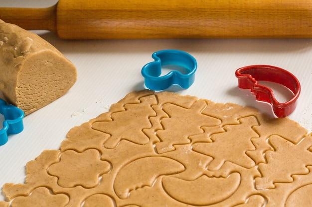Preparare l'impasto per cuocere i biscotti di pan di zenzero a forma di stelle, albero, orso, mese e mattarello