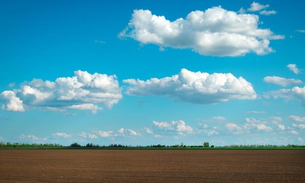 Preparazione del campo per la semina. terreno arato in primavera e cielo nuvoloso blu.