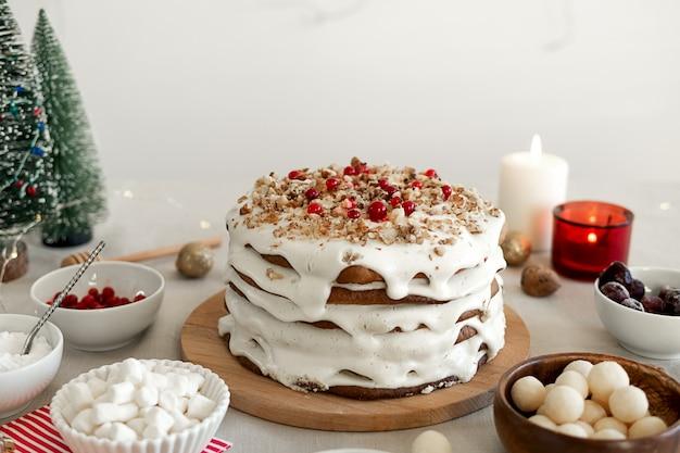 Preparare il cibo per la cena di natale torta fatta in casa con zucchero a velo bianco noci e mirtilli rossi