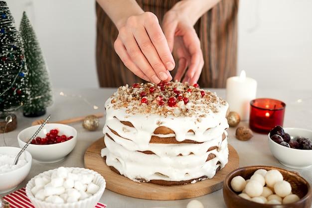 Preparare il cibo per la cena di natale le mani delle donne sono decorate con una torta di natale fatta in casa ai frutti di bosco