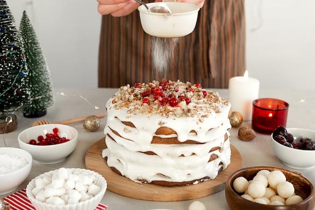 Preparazione del cibo cena di natale le mani delle donne vengono cosparse di zucchero a velo attraverso la torta al setaccio