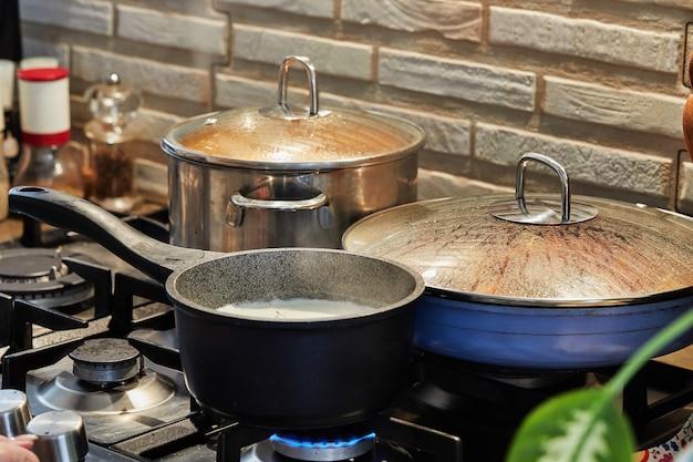 Preparazione del cibo in padella e casseruole sul fornello a gas in cucina. concetto di cucina casalinga.