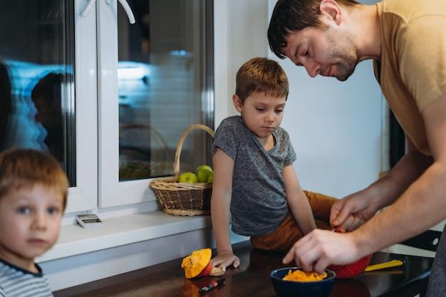 Preparazione per la celebrazione di halloween. uomo caucasico con il suo simpatico figlio di 6 anni che disegna gli occhi su una zucca per realizzare la tradizionale lanterna jack. immagine con messa a fuoco selettiva. foto di alta qualità