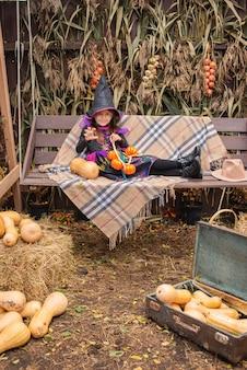 Preparazione per halloween una ragazza vestita come un vestito da strega cattiva e un grande cappello è di buon umore