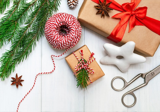 Preparazione per le vacanze, confezionamento di regali, vista dall'alto con spazio di copia. confezioni regalo in carta artigianale, corda a strisce, biscotti festivi e un ramo di un albero di natale su un tavolo di legno bianco.