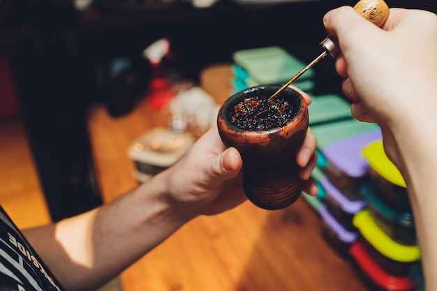 Preparare il narghilè per fumare, riempire la ciotola di argilla con tabacco, mani maschili visibili.
