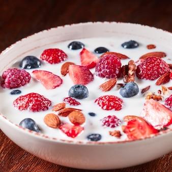 Preparazione della colazione naturale con ingredienti biologici freschi - bacche, muesli, noci, miele e versando il latte in una ciotola bianca su un tavolo di legno. mangiare vegetariano detox