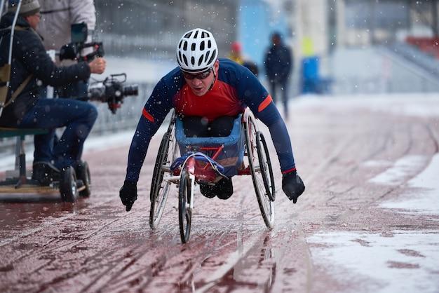 Prepararsi per le paralimpiadi. determinato atleta maschio con disabilità che partecipa a gare di corsa su sedia a rotelle su pista all'aperto durante la nevicata