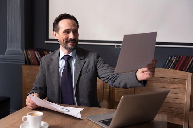 Preparare una presentazione. bel uomo fiducioso felice che tiene un foglio di carta e lo guarda mentre si prepara alla presentazione