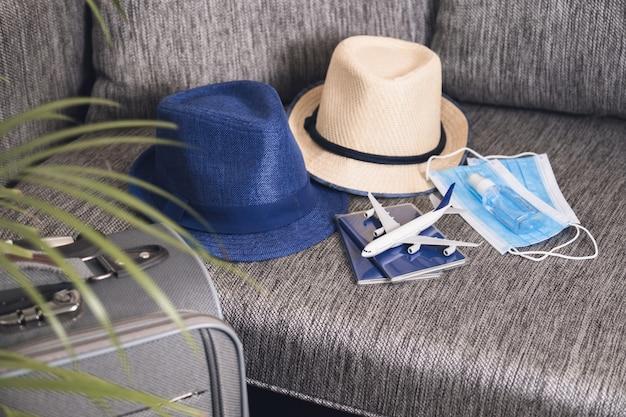 Prepararsi per viaggiare in caso di pandemia. passaporti, cappelli, maschere per il viso e disinfettante per le mani. regole di volo durante la pandemia di coronavirus.