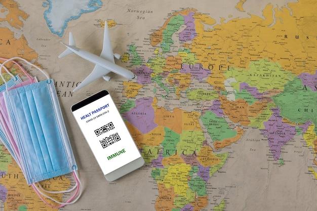 Prepararsi per un viaggio dopo la vaccinazione covid-19 nel telefono cellulare con un certificato di vaccinazione digitale su una maschera medica prima del viaggio sulla mappa del mondo
