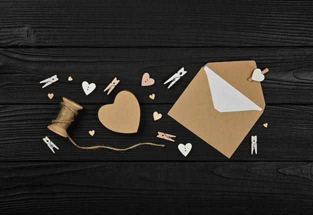 Preparare i regali di san valentino, scatola di carta marrone, cuori, spago, mollette e busta di carta sul fondo della tavola in legno nero, vista dall'alto in alto, direttamente sopra