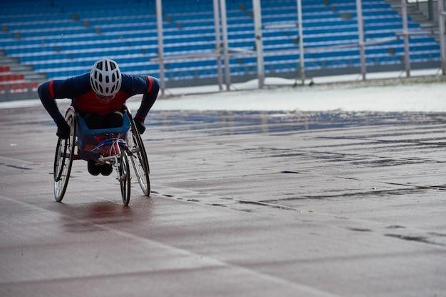 Prepararsi per la maratona in sedia a rotelle. determinato sportivo paraplegico che corre in handbike allo stadio di atletica leggera all'aperto in un cupo pomeriggio piovoso