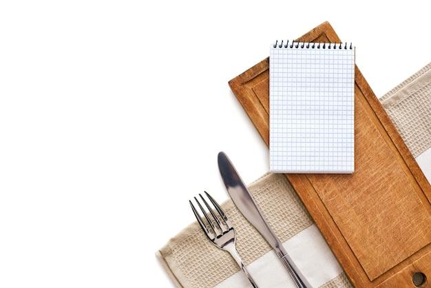 Prepararsi a scrivere la ricetta. taccuino, scrivania in legno, forchetta e coltello sono sdraiati al tavolo. foto ritagliata