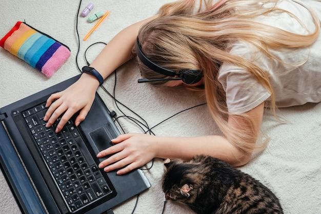 Preparando per gli esami un'adolescente stanca in cuffie che dorme dal suo laptop con il suo gatto domestico