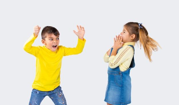 Ragazzo prescolare spaventa la sua ragazza su uno sfondo bianco. il concetto di emozioni e il tempo trascorso dai bambini.