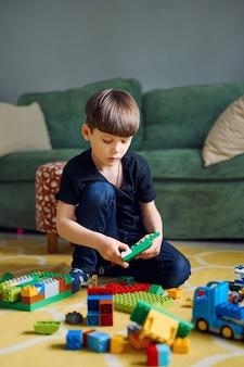 Ragazzo caucasico prescolare che gioca con il costruttore seduto sul pavimento, un sacco di costruttore di blocchi di plastica colorati