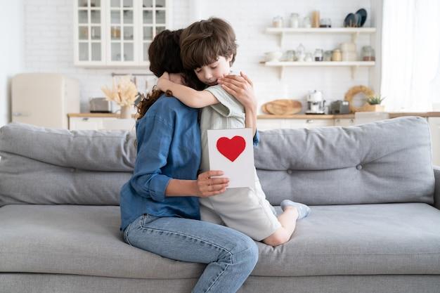 Bambino in età prescolare che abbraccia la mamma tiene il biglietto di auguri bambino che si congratula con la mamma presente cartolina