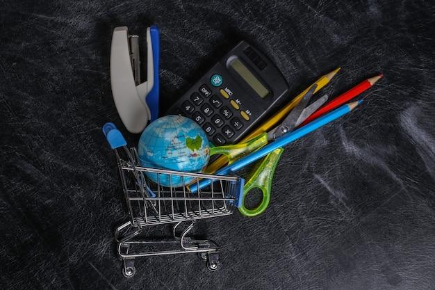 Shopping prescolare. carrello del supermercato con materiale scolastico su una lavagna.