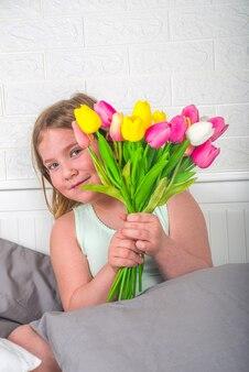 Ragazza bionda del bambino del bambino in età prescolare del bambino con un mazzo dei fiori del tulipano, spazio della copia