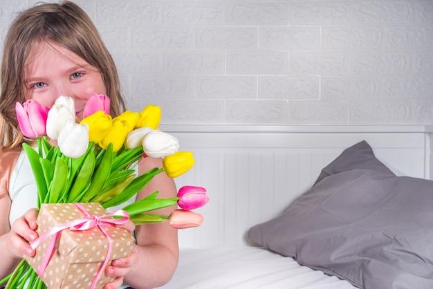 Ragazza bionda del bambino del bambino del bambino in età prescolare con un mazzo dei fiori del tulipano e dello spazio della copia del contenitore di regalo
