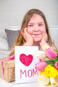Ragazza bionda del bambino del bambino in età prescolare del bambino con un mazzo dei fiori del tulipano, della carta fatta a mano e dello spazio della copia del contenitore di regalo