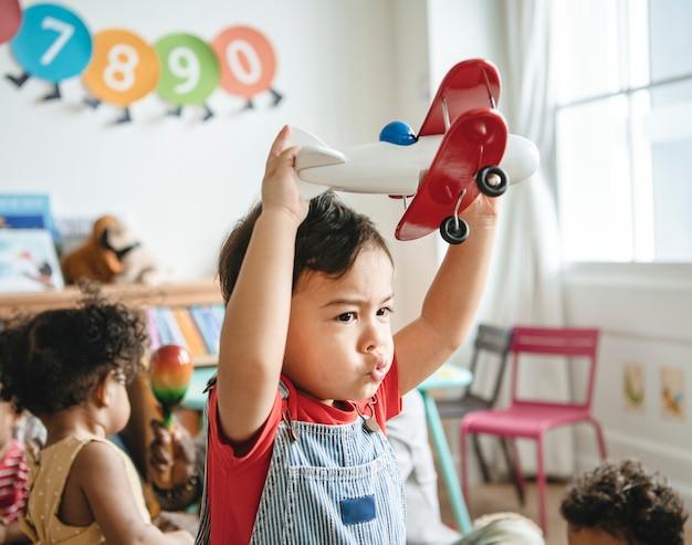 Bambino in età prescolare godendo giocando con il suo giocattolo aereo