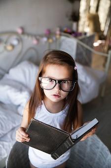 Ragazza del bambino in età prescolare con libri e occhiali. insegnamento, studente, educazione
