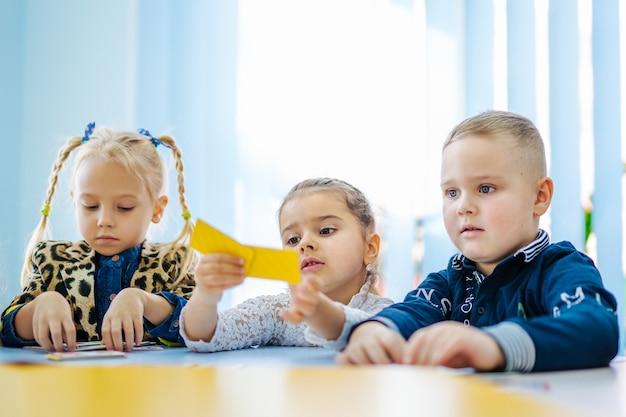Bambini in età prescolare seduti al tavolo in aula. concetto di educazione dei bambini.