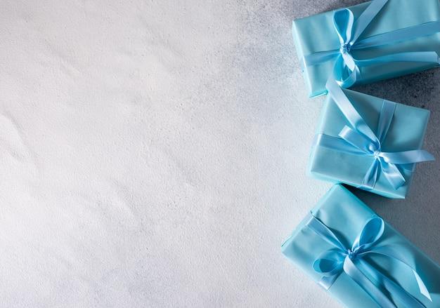 Presente casella con fiocco blu isolato su sfondo grigio