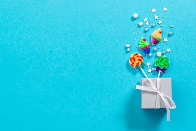 Scatola regalo con decorazioni luminose e coriandoli brillanti su sfondo blu pastello