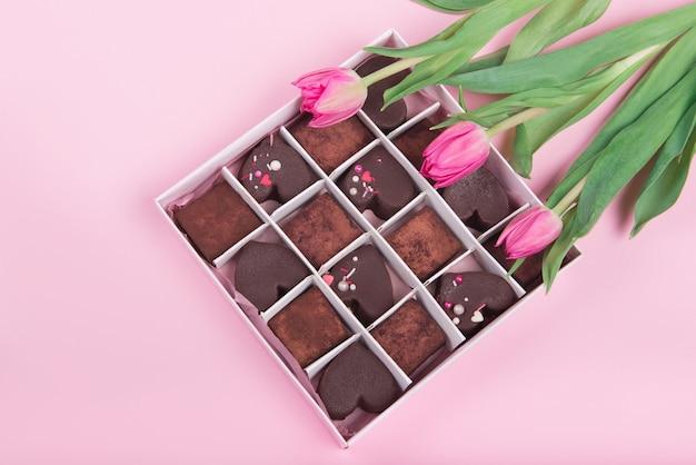 Presente scatola con cuori di dolci al cioccolato e tulipani su sfondo rosa. deserto per san valentino