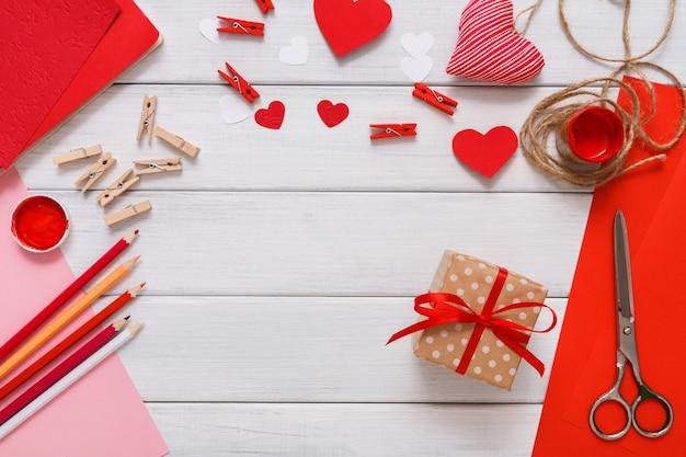 Presente in confezione regalo creazione, cuori, carta artigianale, pittura e strumenti fai da te su legno bianco