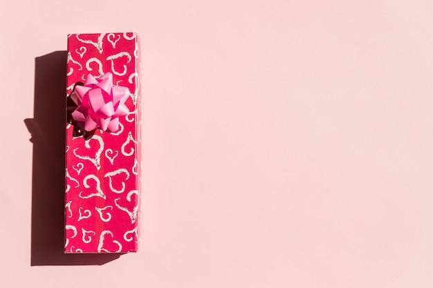 Scatola regalo o regalo, cuore di carta e fiocco rosa vista dall'alto del nastro.